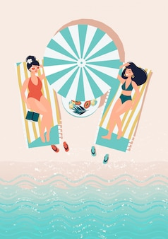 Two friends are lying on sun loungers by the sea under a sun umbrella