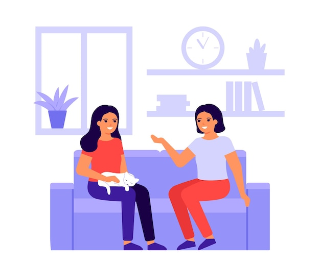Two fun women friends talk at home on couch.
