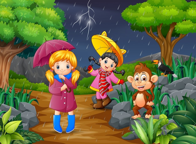 Two girl carrying umbrella goes under a rain with monkey