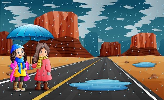 雨の中で傘を持っている2人の女の子