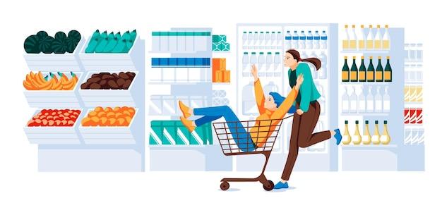 Две девушки в тележке супермаркета едут в супермаркете полки холодильника витрины добра