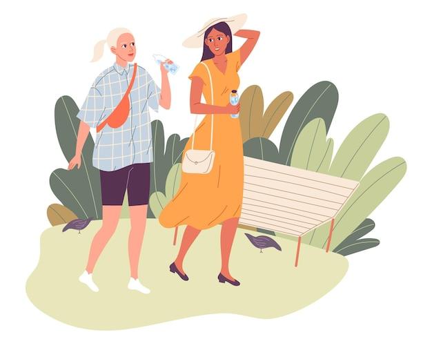 뜨거운 여름에 공원에서 산책에 두 여자. 걷고, 이야기하고, 물을 마시는 친구.