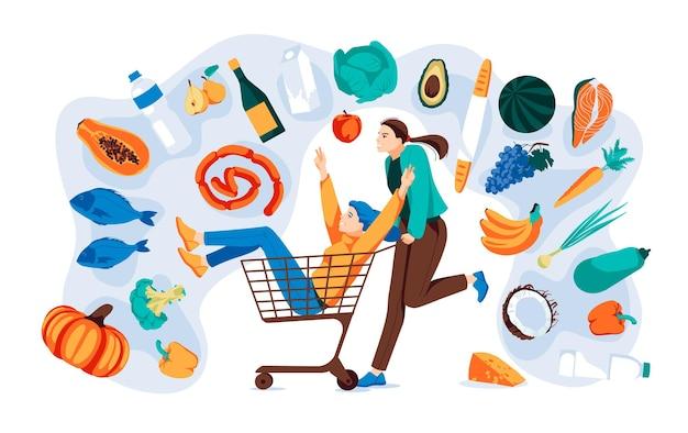 2人の女の子がスーパーマーケットのトロリーに乗って、たくさんの商品が新鮮な果物や野菜を飲みます