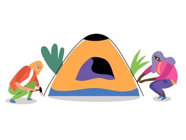 두 여자가 텐트를 치고 여름 하이킹 숲 여행에 영감을 줍니다.