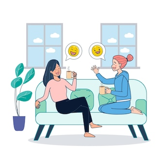 Two girls sitting on couch dringking coffee and gossiping inside home.