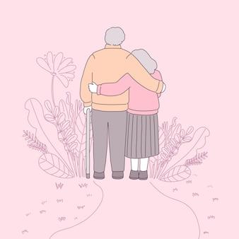 긴 소매를 입은 두 명의 조부모가 꽃밭에서 함께 걸었습니다.