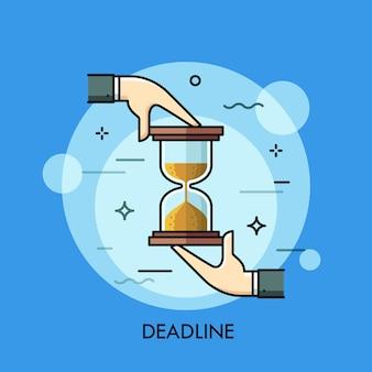 砂時計または砂時計を持っている両手。締め切り、時間制限、タスク管理、事業計画の概念