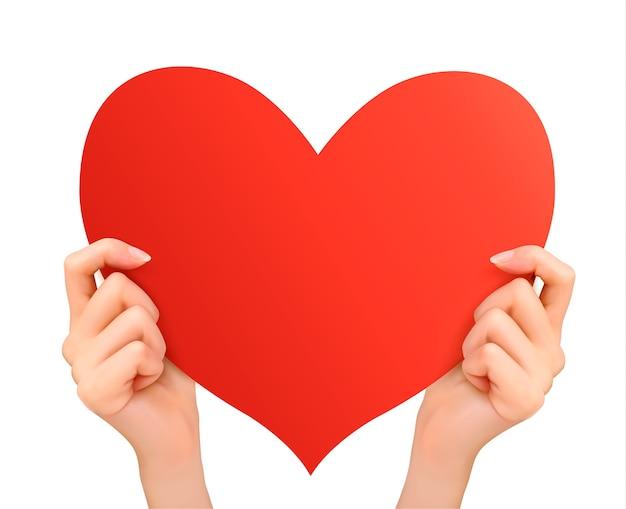 Две руки держат красное сердце.