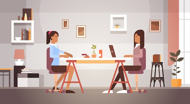 Two indian business woman sitting desk working laptop computer businesswoman office