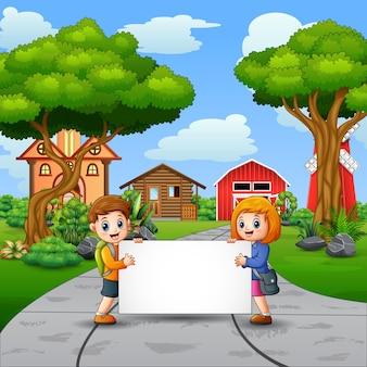 시골 배경에서 빈 기호를 들고 두 아이