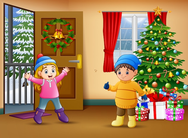 Two kids in the living room with christmas tree decorating