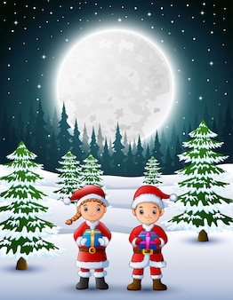 Two kids in santa claus holding a gift box with winter background at night