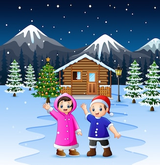 Two kids waving hand in front of the snowy wooden house
