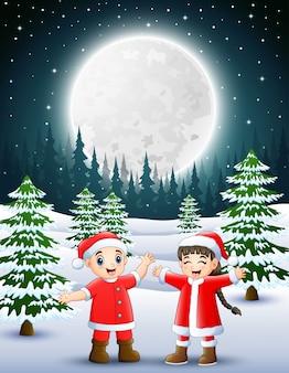 赤いサンタを着て2人の子供が雪の庭で手を振って笑っている