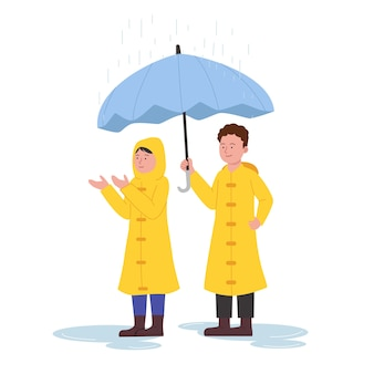 Two kids wearing raincoat standing under rain with umbrella