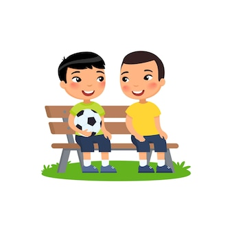 Two little asian boys with soccer ball sit on bench