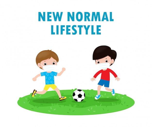 新しい通常のライフスタイルコンセプトでサッカーをしてフェイスマスクを身に着けている2つの小さな男の子サッカーをしていて外科用保護具を着た子供たちコロナウイルス2019-ncovまたはcovid-19