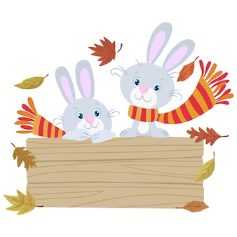 Two little funny rabbits dressed in woolen scarf in autumn