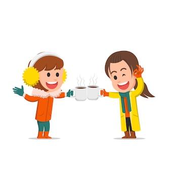 겨울 옷에 핫 초콜릿을 마시는 두 어린 소녀