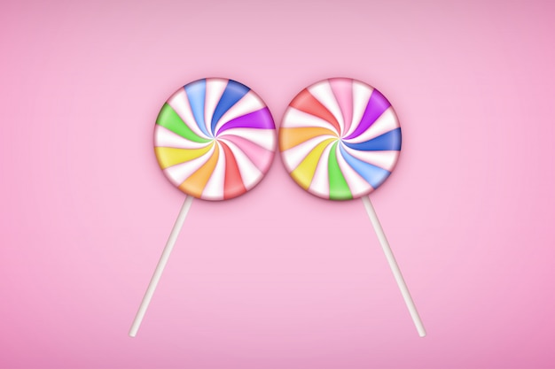 Two lolipops candy on pastel pink background.