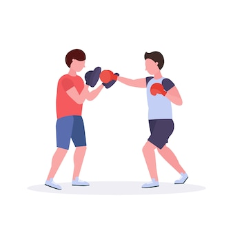 Two men boxers exercising thai boxing in red gloves couple fighters practicing at the fight club healthy lifestyle concept  white background