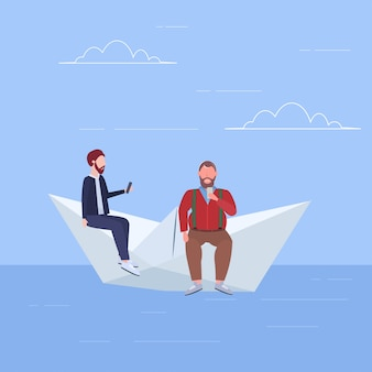 Two men floating on paper boat guys using gadgets traveling together digital addiction web surfing concept full length flat