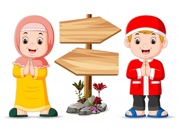 The two muslim children are standing near the wooden signpost