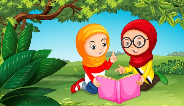 Two muslim girls reading book in park