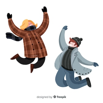 Two people wearing winter clothes jumping