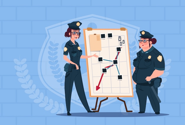 Two police women planning action on white board wearing uniform female guards on blue bricks background
