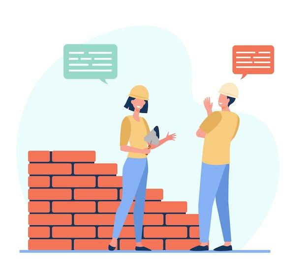 Два позитивных строителя разговаривают и работают