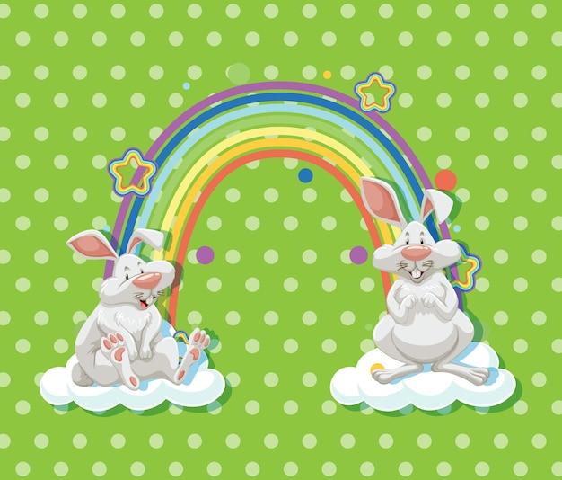緑の水玉模様の背景に虹と雲の上の2匹のウサギ