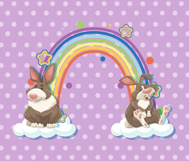 紫の水玉模様の背景に虹と雲の上の2匹のウサギ