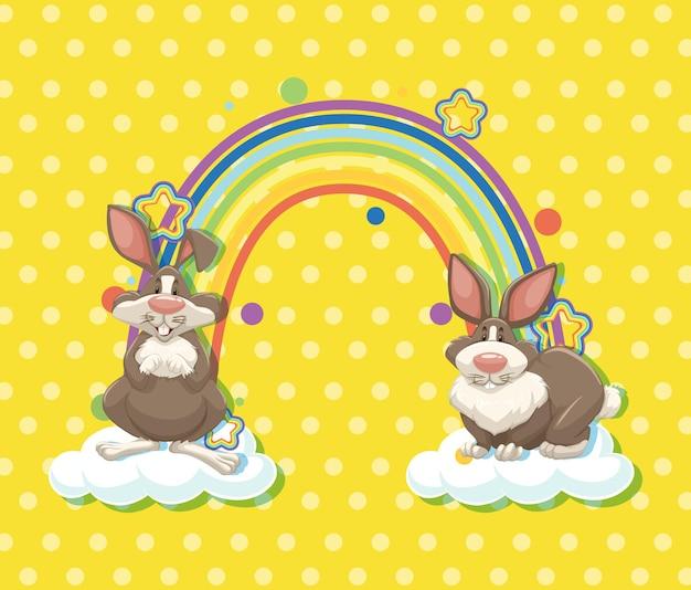 黄色の水玉模様の背景に虹と雲の上の2匹のウサギ