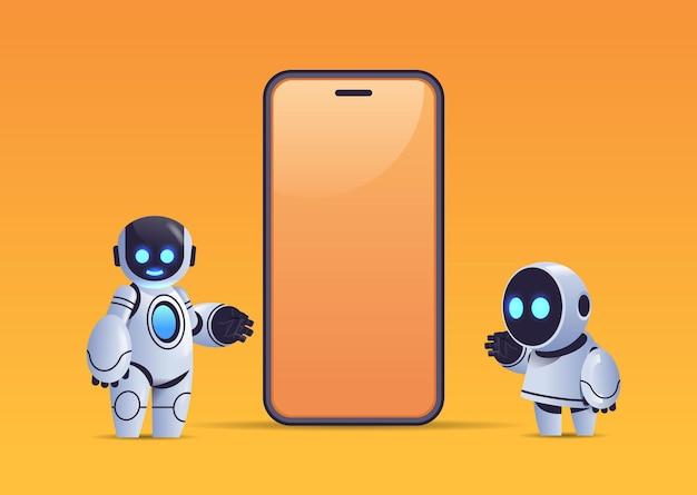 空白の画面のロボットキャラクター人工知能技術でスマートフォンの近くに立っている2台のロボット