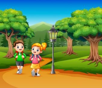 2人の学校の子供たちが森林の道を歩いています