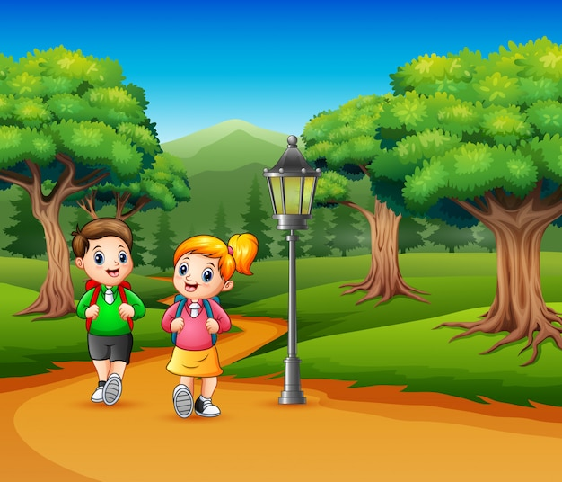 Two school children are walking on the road a forest