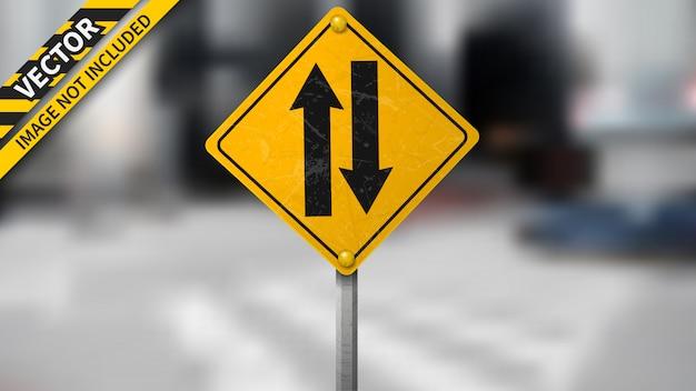 Двухсторонний дорожный знак на размытом фоне