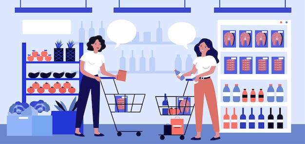 슈퍼마켓에서 이야기하고 제품을 선택하는 두 여자