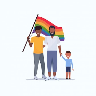 Two young fathers gays with son holding rainbow flag gay same sex african american couple with boy love parade lgbt pride festival concept flat full length