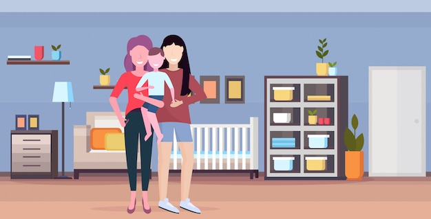 Two young mothers lesbians holding little daughter lgbt lesbian same sex couple with girl happy family having fun modern bedroom interior flat full length horizontal
