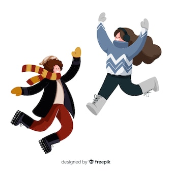 Two young people wearing winter clothes jumping