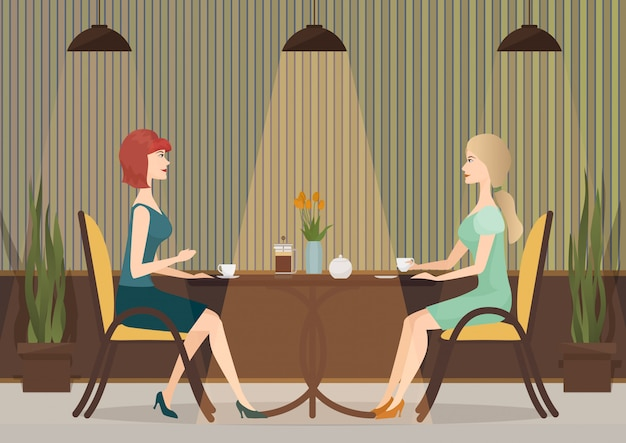 Two young women drinking coffee in the cafe