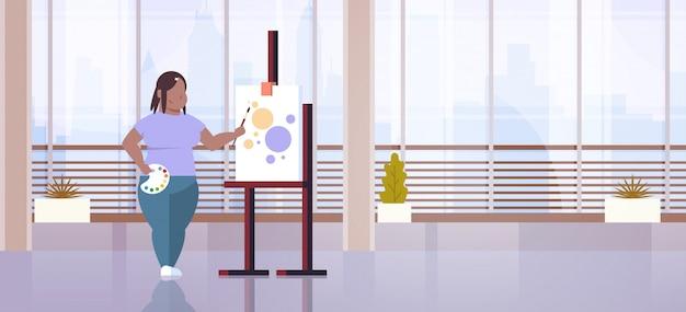 ペイントブラシの女の子アーティスト絵画プロセスアートワークショップスタジオインテリアを保持しているty女性画家 Premiumベクター