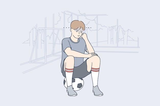 Подавленный разочарованный ребенок футболист сидит на мяч
