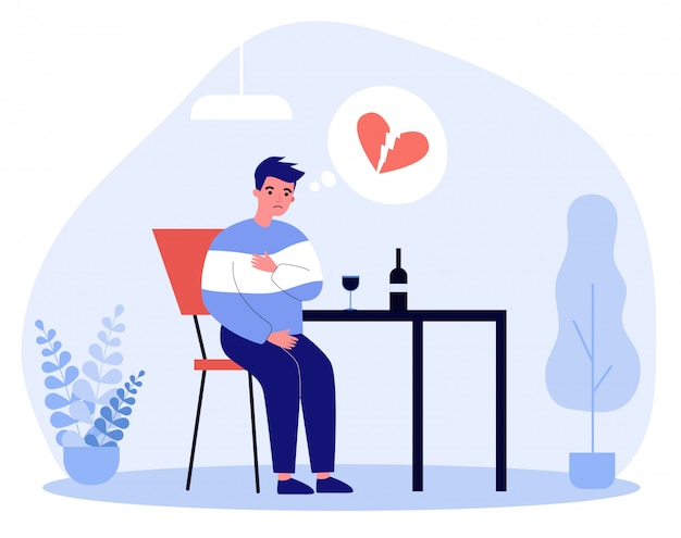 Unhappy man with broken heart drinking wine alone