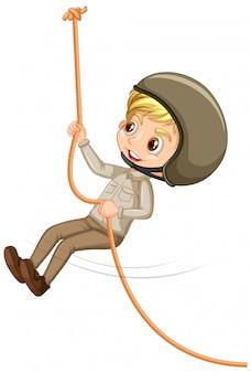 白い背景の上のロープを登るスカウトunifromの少年