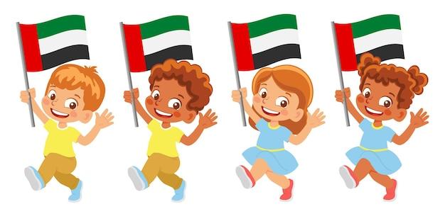 Флаг объединенных арабских эмиратов в руке. дети держат флаг. государственный флаг объединенных арабских эмиратов