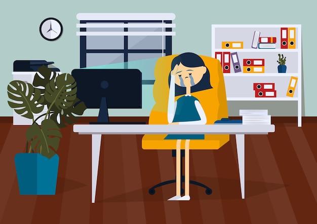 Расстроенная деловая женщина сидит на офисном стуле за компьютерным столом. она плачет и вытирает слезы.