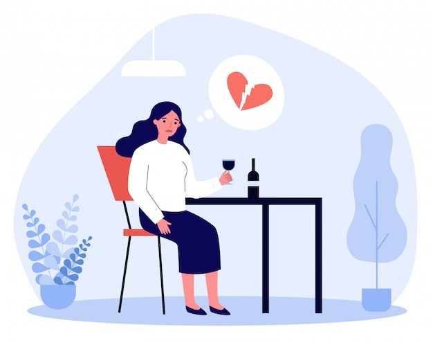Upset woman with broken heart drinking wine